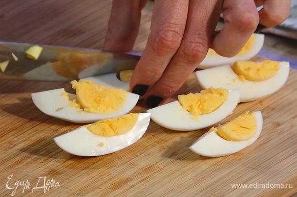 Яйца разделить на дольки. Нарезать укроп и петрушку.