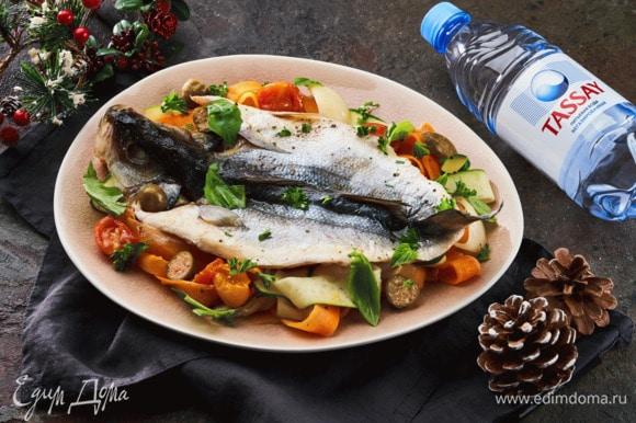 Подавайте рыбу, полив соусом с овощами и украсив петррушкой и базиликом.