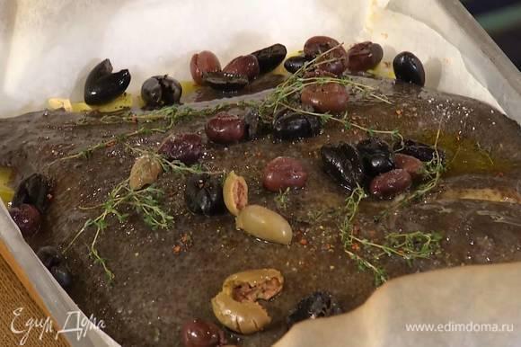 На запеченный картофель выложить камбалу, полить оставшимся оливковым маслом, разложить сверху оливки, оставшиеся веточки тимьяна, посолить, посыпать черным перцем и чили, сбрызнуть вином.