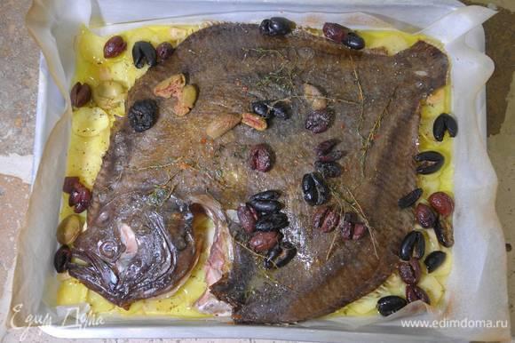 Понизить температуру в духовке до 170°С и запекать рыбу до готовности.