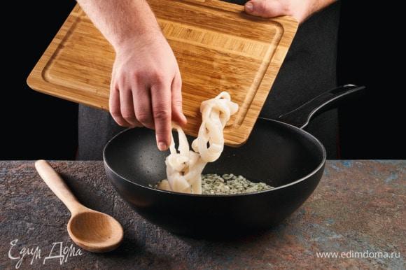 На сковороде в масле обжарьте лук до золотистого цвета. Добавьте кальмаров к луку,