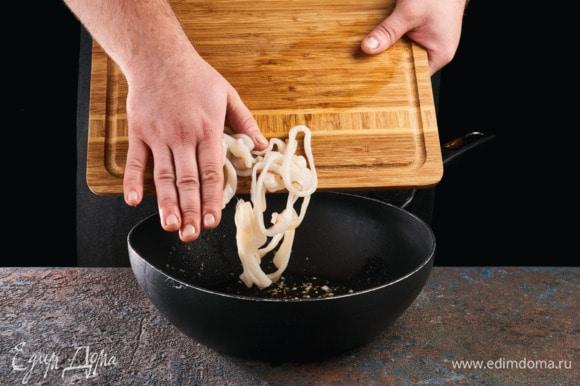 В сковороде разогрейте растительное масло и выложите чеснок. Обжаривайте его 1 минуту до появления аромата. Добавьте в сковороду кальмары и обжаривайте, помешивая, до готовности. Готовых кальмаров обсушите салфеткой, удалив чеснок и лишнее масло.