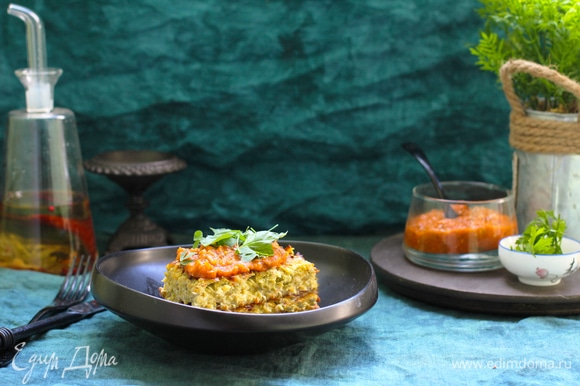 Пока запеканка из кабачков с сыром запекается, приготовьте соус из помидоров. Для этого чеснок очистите и мелко нарежьте. Мелко нарежьте всю пряную зелень. Помидоры бланшируйте в кипящей воде, 2 минуты. Сразу же обдайте холодной, а лучше ледяной, водой и снимите кожицу, сделав надрез крест-накрест внизу помидора. Для запеканки из кабачков выбирайте мясистые помидоры без избытка сока. Разрежьте помидоры пополам, удалите сок и семена. Они для приготовления этого блюда не нужны. Мякоть помидоров нарежьте мелкими кубиками. Луковицу нарежьте таким же образом, как и для запеканки. Обжарьте нарезанный лук на среднем огне с оставшимся оливковым маслом до золотистого цвета, 6–7 минут. Добавьте чеснок, пряные травы, сахар. Посолите и поперчите. Сковороду снимите с огня. Дайте ему настояться, 10–20 минут. Измельчите блендером и охладите до комнатной температуры. Подавайте запеканку теплой или остывшей с соусом.
