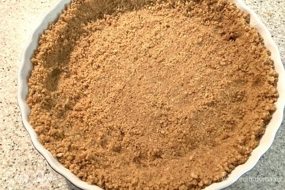 Духовка — на 180°C. Печенье — в крошку при помощи блендера. Масло растопить. Все смешать. Диаметр формы — 22 см. Выложить крошку, хорошо примять. Выпекать 10 минут. Достать, поставить охлаждаться.