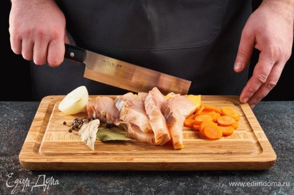Нарежьте рыбу порционными дольками. Лук разрежьте пополам, морковь нарежьте кружочками.