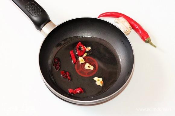 На разогретом оливковом масле обжариваем нарезанные перчик чили и чеснок. Затем овощи удаляем, масло оставляем.