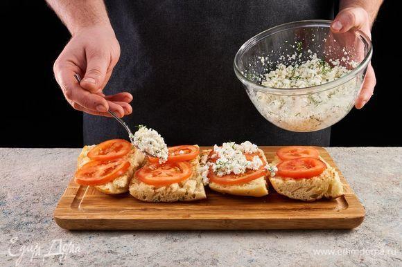 Выложите на каждый кусочек хлеба помидор и творожную смесь.