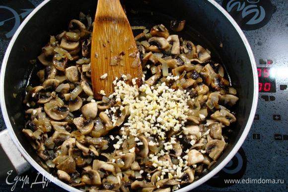 Как только грибы и лук будут готовы, всыпать оставшуюся часть мелко нашинкованного чеснока. Перемешать, посолить, поперчить и слегка обжарить. Снять с огня и слегка остудить.