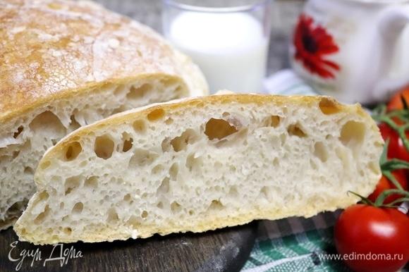 Достать хлеб, «умыть» его водой, прикрыть полотенцем и оставить на решетке остывать хотя бы на полчаса. Только потом его можно разрезать. Корочка тонкая, хрустящая. Мякиш пузырчатый, эластичный. Если его смять, то он с легкостью распрямляется. Хлебушек не влажный и не сухой, дрожжами не пахнет, вкус настолько сбалансирован, что придраться не к чему. Муж любит черный хлеб, но этот белый ему очень нравится.
