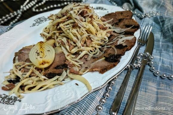 Горкой выложите лапшу с мясом на блюдо. По краям украсьте блюдо тонко нарезанными ломтиками мяса или казы. Добавьте лук полукольцами, замаринованный заранее. По желанию налейте горячий бульон в пиалы. Праздничная закуска готова. Приятного аппетита.