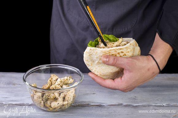 В питу положите салатный лист, кольца красного лука, помидоры и обжаренные кусочки курицы.