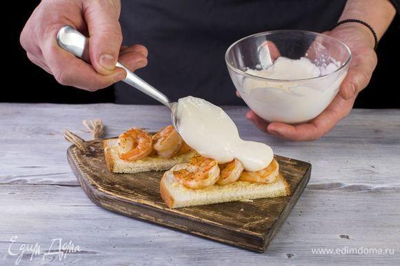 На хлеб выложите креветки. Сверху полейте сливочно-лаймовым соусом.