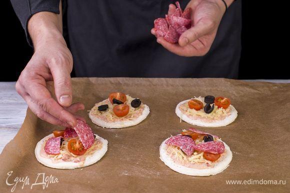 Выложите салями. Поставьте в разогретую до 180°С духовку на 25 минут.