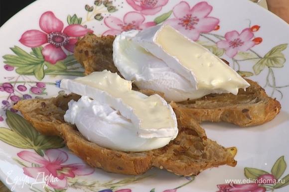 На тарелки выложить половинки круассана, сверху — яйцо, на него сыр бри и бекон.