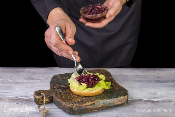 Положите салатный лист, затем — половину лука.