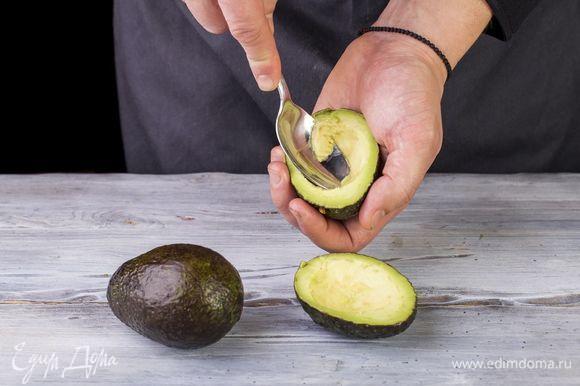 Авокадо разрежьте пополам и вытащите косточку. Удалите немного мякоти авокадо. Сыр натрите на крупной терке.