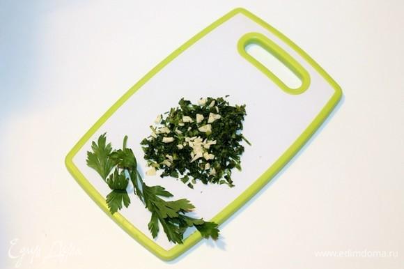 Приготовим заправку для риса. Моем и мелко режем петрушку и руками перетираем с маленькой щепоткой соли до выделения сока. Добавляем очищенный и нарезанный чеснок.