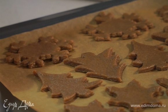При помощи формочек для печенья вырезать из теста фигуры, выложить их на застеленный пергаментом противень. В фигурках сделать маленькие отверстия для веревочек. Выпекать в духовке при 180°С в течение 12 минут.