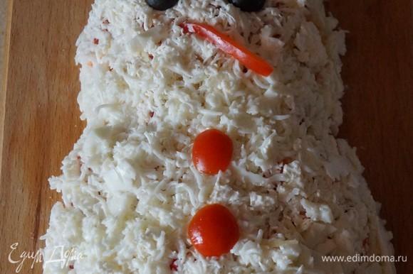 Далее нужно посыпать салат тертым пармезаном, мягким сыром, сверху натереть яичный белок. Украсить «глазками», «пуговками» и «ротиком» из оливок, перца и помидоров.