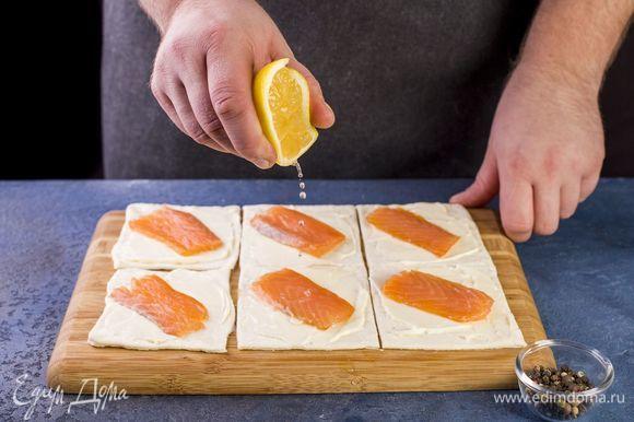 Выложите ломтик рыбы, сбрызните лимонным соком и поперчите.