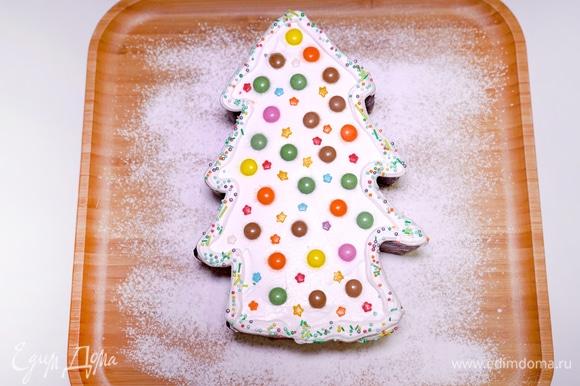 Перекладываю остывшую выпечку на деревянную тарелку. Я посыпала ее сахарной пудрой. Украшаю поверхность елочки взбитыми сливками. Сверху на сливочную прослойку кладу разноцветные конфетки с шоколадной начинкой — это и есть наши елочные игрушки. Помимо этого, украшаю елочку кондитерскими посыпками в форме милых звездочек, чтобы наша выпечка засияла праздничными огнями.