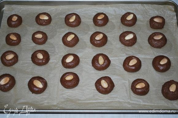 Из теста сформируйте шарики, в серединке шарика утопите миндальный орешек. Выпекайте печенье в разогретой духовке при 170°C примерно 15 минут. Долго его в духовке не держите, чтобы не пересушить.