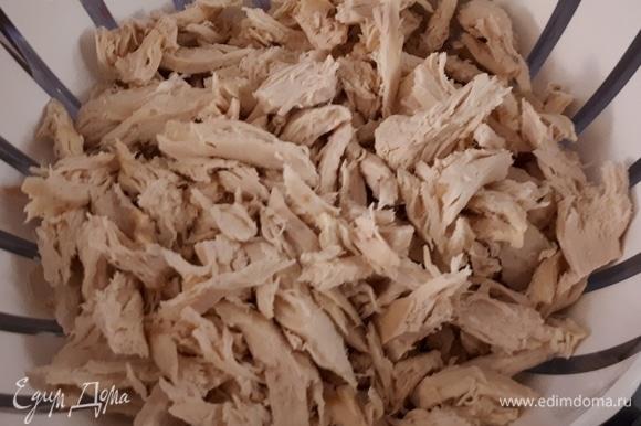 Сварите куриные грудки, затем нарежьте их на небольшие кусочки.