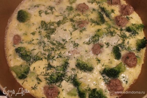Сковороду немножко смазываем сливочным маслом, выкладываем брокколи и фрикадельки. Все заливаем молочно-яичной смесью. Сверху посыпаем мелко нарезанным укропом. Прикрываем крышкой и готовим 5 минут. Блюдо готово! Для подачи можно использовать свежие овощи и хлеб. Приятного аппетита.