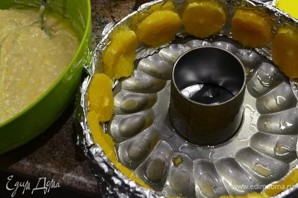 Подготовим форму для выпечки: по бортику проложить пергаментом или фольгой, смазать маслом. Разрезаем апельсин и кружками выкладываем по кругу бортика.