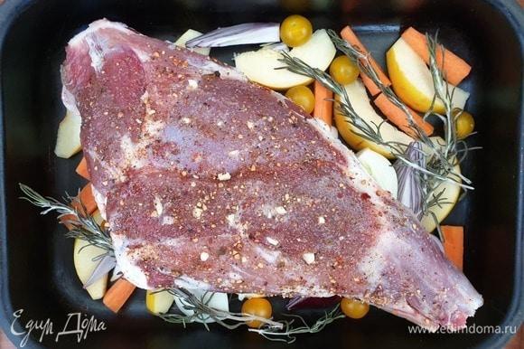 На овощную подушку выложите баранью ногу и розмарин. Влейте в форму для запекания воду. Воды должно быть столько, чтобы она не касалась бараньей ноги. Разогрейте духовку до 220°C. Запекайте мясо в течение 40 минут.