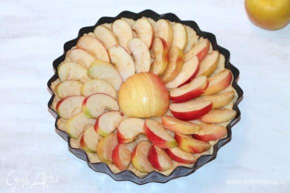 Полуготовый корж вынуть из духовки и распределить яблоки.