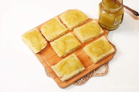 Полностью остывшие квадратики разрезаем на 2 части и смазываем джемом. Выкладываем пирожные на блюдо и посыпаем кокосовой стружкой.