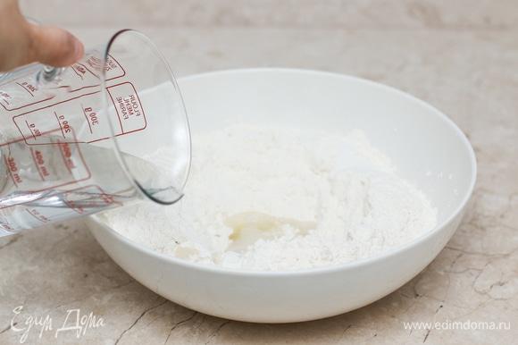 В широкой миске смешайте все ингредиенты для теста. Мука у всех разная, поэтому наливайте воду постепенно. Замесите не очень тугое тесто. Накройте миску с тестом пленкой или полотенцем и оставьте отдыхать на 10–15 минут. Здесь важно обратить внимание на температуру теста, она должна быть около 60°C.