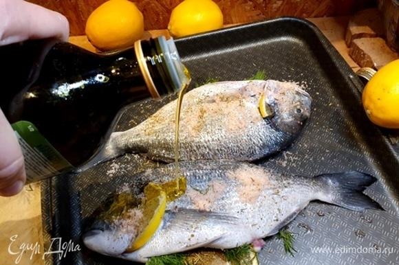 Поливаем сверху оливковым маслом. Можно обработать маслом всю рыбу, со всех сторон.
