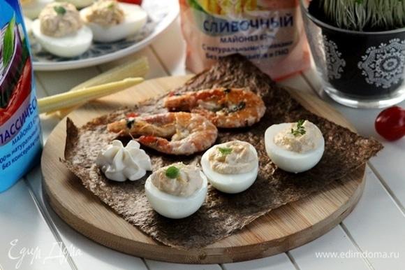 Обжаренные креветки и яйца с наполнением выкладываем на блюдо, на лист нори, украшаем майонезным цветочком, зеленью. Можно подать дополнительно овощи на гриле, которые вы предпочитаете.