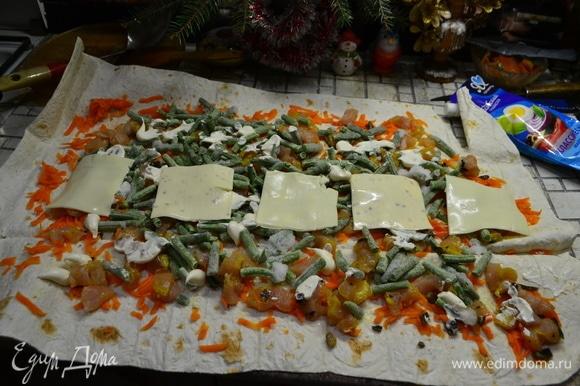 Слоями выкладываю отварную морковь, натертую на терке, кусочки куриной грудки, нарезанной на кубики, фасоль зеленую, майонез и сверху в ряд пластинки сыра. Сворачиваем в рулет.
