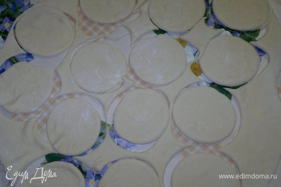 Тесто для вареников раскатать в тонкий пласт на подпыленном мукой столе. Стаканом вырезать кружки.