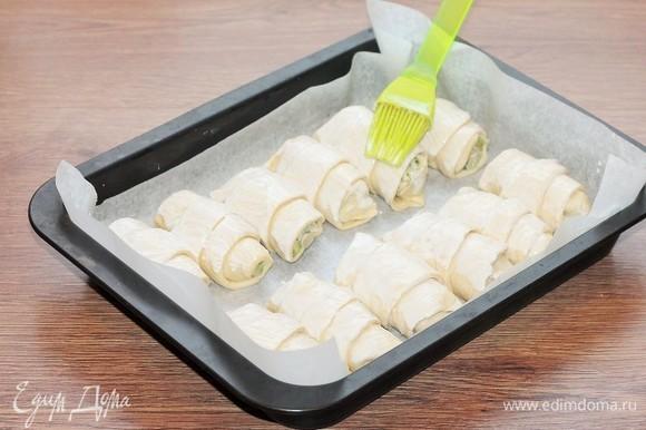 Выкладываем рогалики на противень и смазываем жидкой сметаной (жирность — 10%). Ставим противень в духовку и включаем минимальную температуру — 40°C. Даем тесту подняться (15 минут). Затем переключаем духовку на 200–220°C и выпекаем рогалики минут 10.