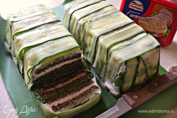 После охлаждения выложите закусочный торт на разделочную доску и с помощью острого ножа нарежьте на порционные куски.