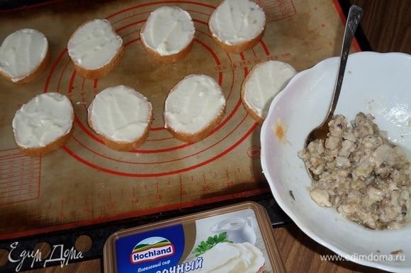 Багет нарезаем на кусочки толщиной примерно 1 см. На каждый кусочек багета выкладываем сливочный сыр и равномерно распределяем. Выкладываем кусочки багета на противень, застеленный пергаментом или силиконовым ковриком.