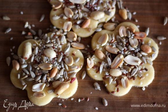 Любыми формочками вырезаем печенье. Смазываю белком для того, чтобы семечки прилипли к тесту и не ссыпались. И посыпаю семечковой смесью. Посыпку слегка придавить пальчиками.