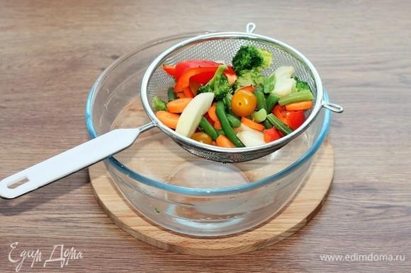 Воду сливаем, овощи выкладываем в сито.