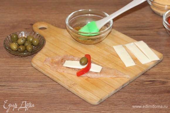 Положите на полоску кусочек сыра и оливку.