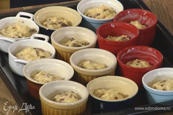 В подошедшее тесто добавить теплые грибы и вымесить его руками, затем разложить в смазанные оставшимся сливочным маслом керамические формочки, заполняя их на 2/3 объема, поместить на противень, накрыть влажным полотенцем и оставить на 15 минут.