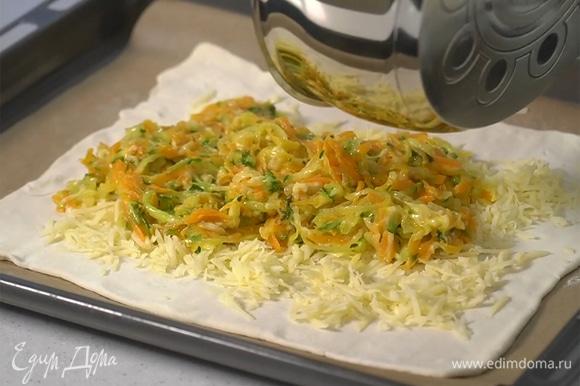 К овощам в сковороде добавить тертый сыр грюйер, перемешать. Выложить начинку на тесто, сверху посыпать тертым мягким сыром.