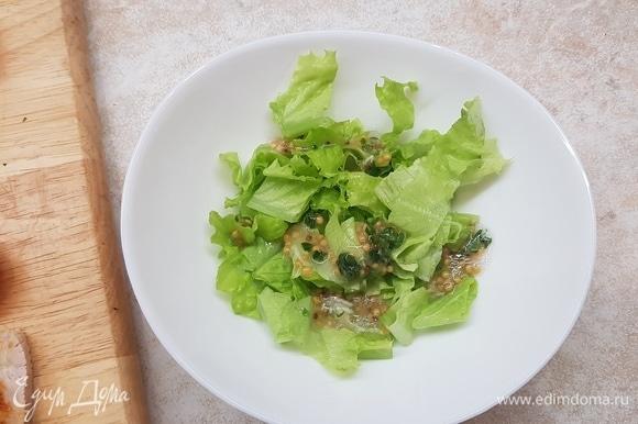 На дно салатника положить салатные листья, полить частью заправки.