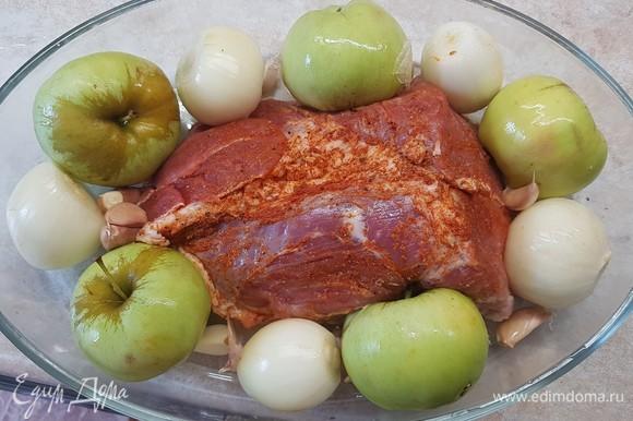 Мясо уложить в форму для запекания. Вокруг куска выложить целые яблоки и луковицы. Чеснок разобрать на зубчики, но не чистить их. Выложить тоже вокруг свинины.
