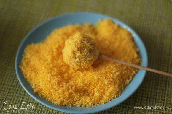Затем шарик обваливаем в желтой кокосовой стружке.
