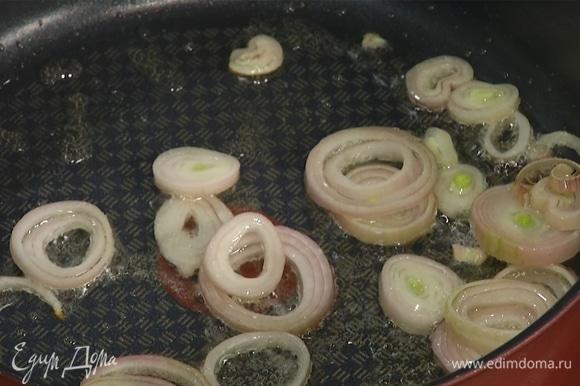 Разогреть сковороду с оливковым маслом. Нарезать лук кольцами, слегка обжарить. Чеснок раздавить плоской стороной ножа, целиком добавить в сковороду.