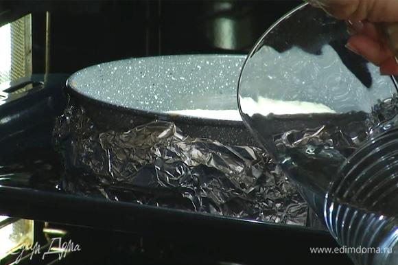 Форму с чизкейком поставить в глубокий противень, задвинуть его на 2/3 в духовку и влить в противень холодную воду так, чтобы форма была покрыта на четверть.